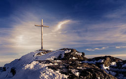 Wooden summit cross on the mountain peak with cloudy clear sky Stock Photography