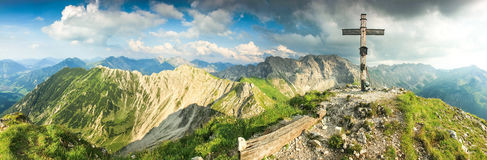 Wooden summit cross and summer colors in mountains. Panoramic view. Stock Photography