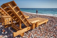 Wooden sun loungers and girl on sea coast Stock Photo