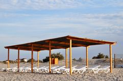 Wooden canopy with sun loungers on the beach at dawn. stock image