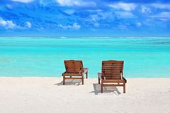 Wooden sun loungers on sea beach. In summer day Stock Photos