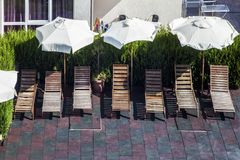 Wooden sun loungers. With white umbrellas near the hotel complex, holiday and vacation concept stock photos
