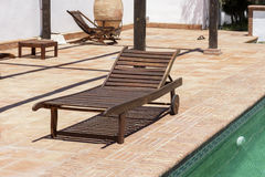 Wooden sun recliner beside a swimming pool Royalty Free Stock Images