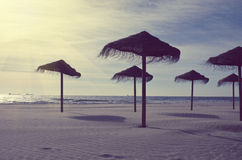 Wooden sun umbrellas silhouettes on the sea beach. Vacation concept in vintage color tone. Royalty Free Stock Images