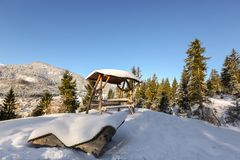 Wooden sunbath lounge bench chair, outdoor picnic table with roo. F under snow on sunny day with blue sky, winter in Tyrol, Europe Stock Photography