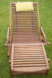 A wooden sunbed on green grass Stock Photo