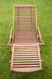 A wooden sunbed on green grass Royalty Free Stock Photos