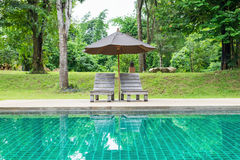 Wooden sunbed with umbrella on modern swimming pool Royalty Free Stock Photo