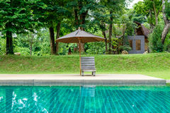 Wooden sunbed with umbrella on modern swimming pool Stock Photography