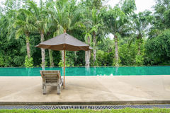 Wooden sunbed with umbrella on modern swimming pool Royalty Free Stock Photography