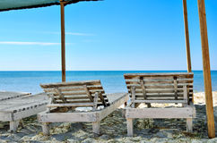 Wooden sunbeds on the background of blue sea. Royalty Free Stock Photography