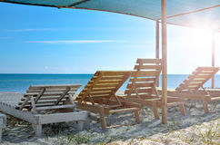 Wooden sunbeds on the background of blue sea. Resorts, vacation and seascapes Royalty Free Stock Photos
