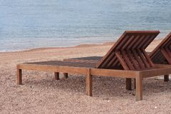 Wooden sunbeds on the beautiful beach near the sea Royalty Free Stock Photo