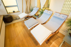 Wooden sunbeds. Wooden comfortable sunbeds in restful room Royalty Free Stock Photo
