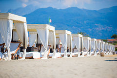 Wooden sunbeds in front of a turquoise sea in the evening light. Sunbeds in famous italian sand beach at Forte dei Marmi Royalty Free Stock Photography