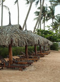 Wooden sunbeds on monsoon beach Stock Images