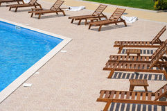 Wooden sunbeds near the pool Stock Photo