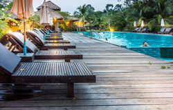 Wooden sunbeds on wooden deck nearby swimming pool in the evening Royalty Free Stock Images