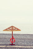 Wooden sunshade and a lifebuoy on the sea beach Stock Photography