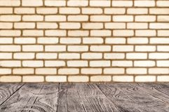 Wooden surface on the background of deorated brick wall royalty free stock photography