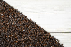 Wooden surface half backfilled with coffee beans Royalty Free Stock Images