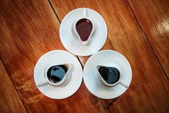 On the wooden surface stand are three bowls with sauces. On the wooden surface stand are three bowls with different sauces Royalty Free Stock Image