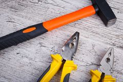 On the wooden surface there is a hammer and two pliers. Close-up. stock photography