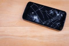 Smartphone with a broken screen. Close-up. On the wooden surface there is a modern black smartphone with a broken screen. Close-up stock photo