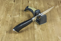 On the wooden surface there is a sharpener and a metal knife wit Stock Photos