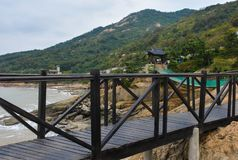 Wooden suspension bridge between mountains and sea Stock Photos