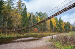 Wooden suspension bridge over the river Stock Photography