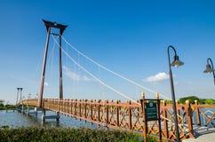 The wooden suspension bridge span that across the small lake at Wareepirom Park. Bangkok, Thailand, The wooden suspension bridge span that across the small lake stock photography