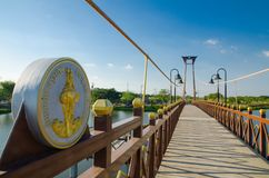 The wooden suspension bridge span that across the small lake at Wareepirom Park. Bangkok, Thailand, The wooden suspension bridge span that across the small lake royalty free stock photo