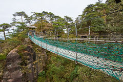 The wooden suspension bridge in valley Stock Photo