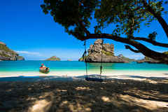 Wooden swing against paradise beach scene Royalty Free Stock Photography