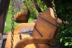 Wooden swing. Beautiful wooden swing in the garden Royalty Free Stock Images