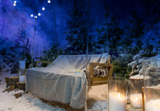 Wooden swing with a blanket and book on it in the evening in a s Royalty Free Stock Photography
