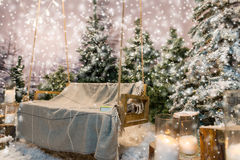 Wooden swing with a blanket and book on it in a snow-covered par Royalty Free Stock Image