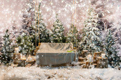 Wooden swing with a blanket in a snow-covered park or a forest, Stock Photography