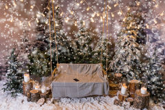Wooden swing with a blanket and telephone on it in a snow-covere Stock Photos