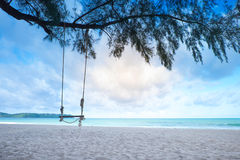 Wooden swing on the blue sea in the morning Royalty Free Stock Photography