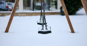 Wooden swing covered with snow Stock Photo