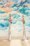 Wooden swing decorated with bouquets of flowers Stock Photo