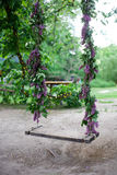 Wooden swing decoreted by branch of lilac Stock Photo