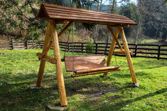 Wooden Swing. A wooden swing in the garden, the perfect place to relax Royalty Free Stock Images