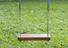 Wooden swing. And green grass background Stock Photo
