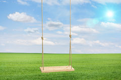 Wooden swing in a green meadow Stock Images