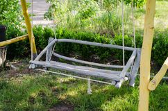 Wooden swing hand-made in the garden. Cozy patio for rest Royalty Free Stock Photography