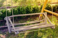 Wooden swing hand-made in the garden. Cozy patio for rest Stock Photos
