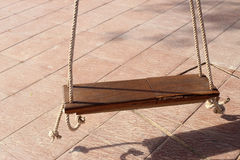 Wooden swing hanging on couple of ropes in warming sunlight.  Royalty Free Stock Photos